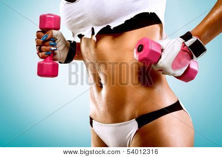 Body of a young fit woman lifting dumbbells