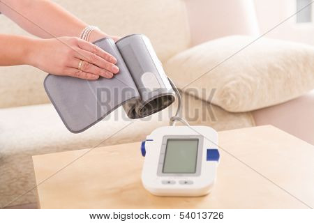 Women's hands with blood pressure monitor cuff