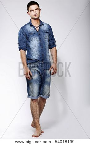 Full Length Portrait Of Young Confident Barefoot Man In Blue Jeans