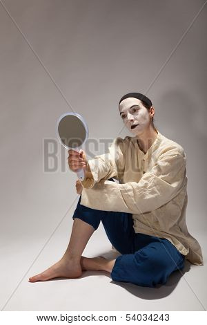 The Clown Is Sitting On The Ground With A Mirror In His Hand