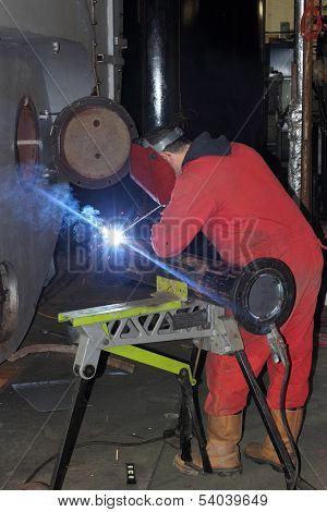 A welder welding a flange onto a pipe