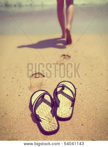 slippers on sand and female feet out of focus with a retro effect