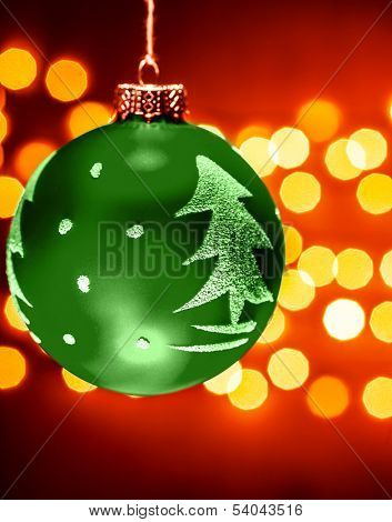 Green Christmastime decoration with Christmas tree ornament, beautiful festive decor on red background with golden blur lights, traditional wintertime toys
