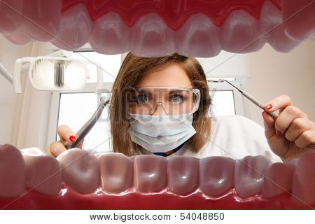 View at young female dentist with dental tools from patient's mouth