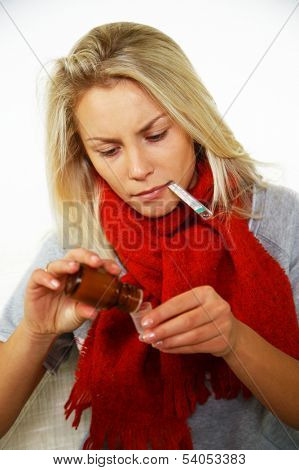 Sick young blond woman with thermometer bottle of mixture