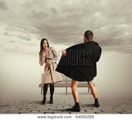 startled young woman looking at exhibitionist in the street