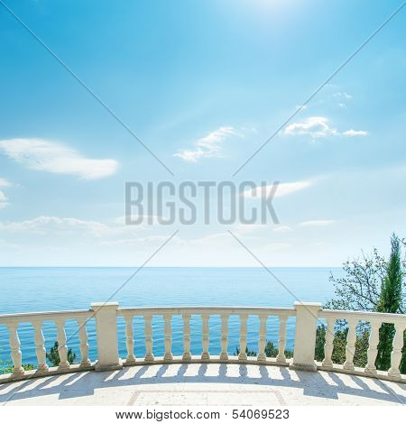 white balcony near sea and light clouds on sky