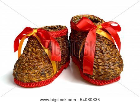 A pair of handmade weaving boots with red ribbon