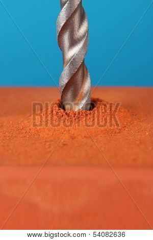 Close-up image of drilling hole on brick, on color background