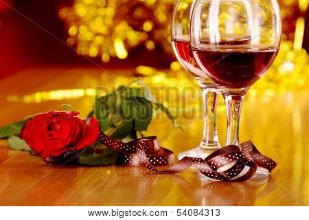 christmass dinner with rose candies and two glasses of red wine