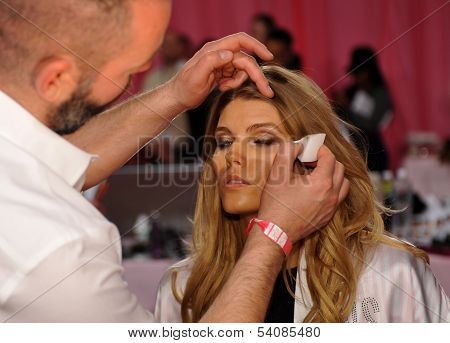 NEW YORK NY - NOVEMBER 13: Lead Makeup Artist Dick Page applying make-up to model Maryna Linchuk