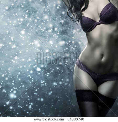 Body of young and beautiful woman in sexy lingerie over the snowy winter background