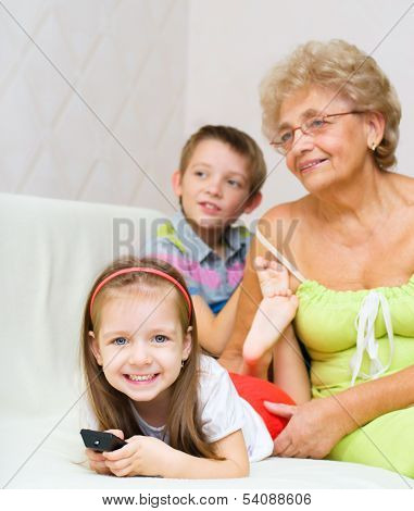 Grandmother With Her Grandchildren Are Watching Tv