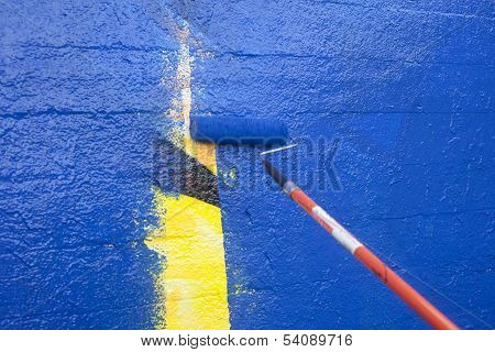 Painting Over Graffiti On A Wall With A Paint Roller