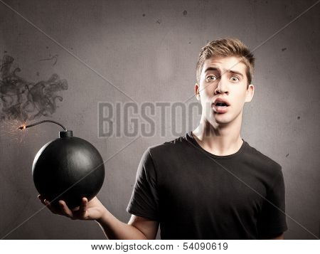 scared young man holding an old fashioned bomb