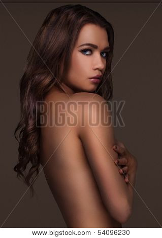 Seductive topless beautiful young woman with long brunette hair standing in the shadows turned sideways looking back at the camera with a sultry look in a tantalising pose
