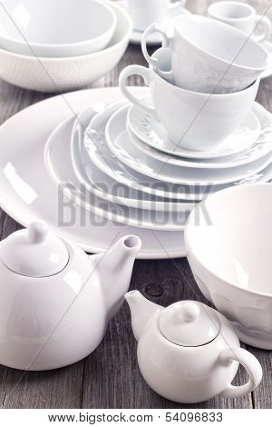 Variety of white dinnerware (cups plates and bowls)
