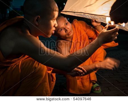 Buddhist Monks Lighting Up Hot Air Balloon at Loi Krathong 2013 Festival