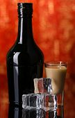 stock photo of bailey  - Baileys liqueur in bottle and glass on red background - JPG