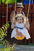picture of naked children  - Toddler girl having fun on the swing while having candy with her bare naked feet and pushed by her grandmother with the hat