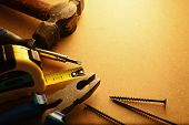 stock photo of semi-circle  - Home maintenance tool kit in a sepia toned image arranged in a semi circle on the border with a hammer pliers screwdriver tape measure and nails surrounding copyspace - JPG