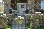 foto of front door  - home entrance to cobblestone house accented by purple blue hydrangea flowers in urns and a hanging pot on a gate - JPG
