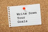 stock photo of reminder  - Write Down Your Goals typed on a scrap of paper pinned to a cork notice board - JPG