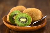 stock photo of flesh  - Kiwifruits on wooden plate with spoon  - JPG
