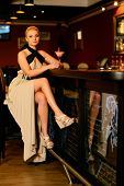 Beautiful blond woman in evening dress sitting near bar counter with cocktail