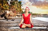 stock photo of padmasana  - Christmas Yoga padmasana lotus pose by young woman in red costume and red christmas hat on the beach near the ocean at sunset background in India - JPG