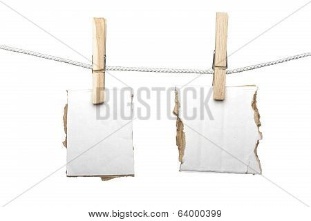 Two Ripped Pieces Of Card Board Hanging On One Clothespins, Isolated On White