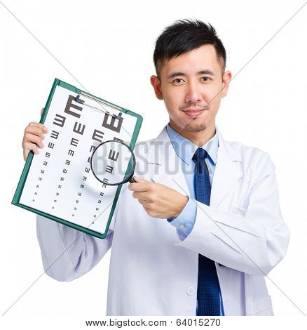 Male doctor holding optometry chart and magnifying glass