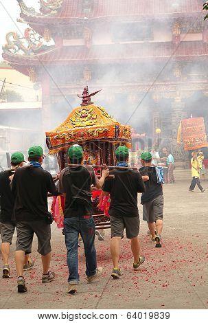Young Men Carry A Sedan Chair Towards A Temple