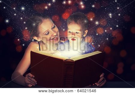 Mother And Child Baby Daughter Reading Magic Book In Dark