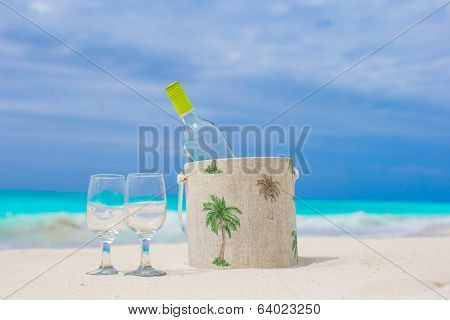 Bottle of wine and two glasses on the white sandy beach