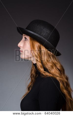Redhead girl in hat against grey background