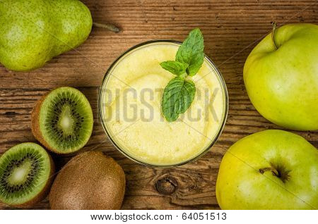 Fruit smoothie with fresh ingredients on a wooden background
