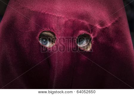 Detail Of Blue Eyes Of Penitent With Caperuz Red During Holy Week In Spain