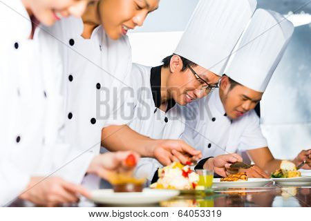 Asian Indonesian chef along with other cooks in restaurant or hotel kitchen cooking, finishing dish or plate for dessert
