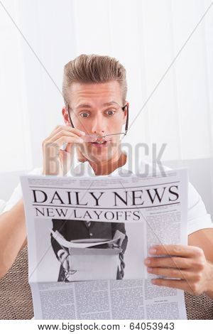 Reading Newspaper With The Headline New Layoffs