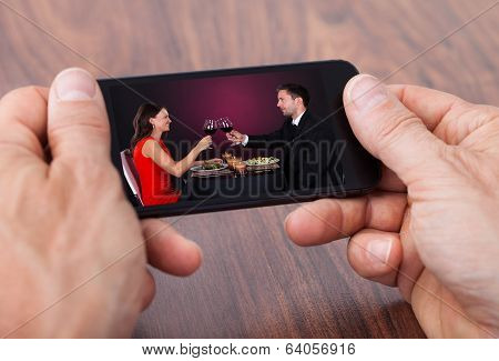 Person Holding Cellphone Watching Video