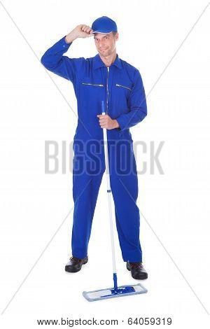 Worker In Boilersuit Cleaning Floor