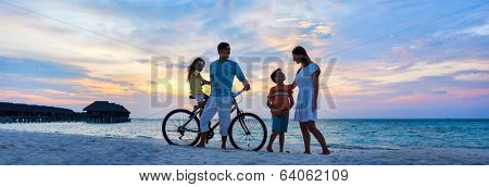 Family with a bike on tropical beach at sunset