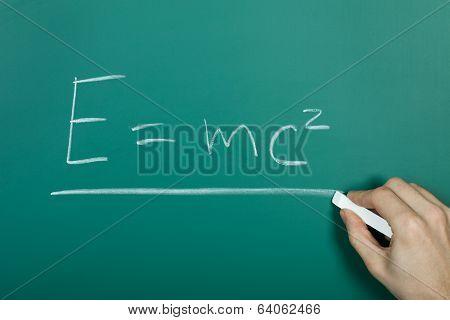 Hand Writing Relativity Formula On Blackboard