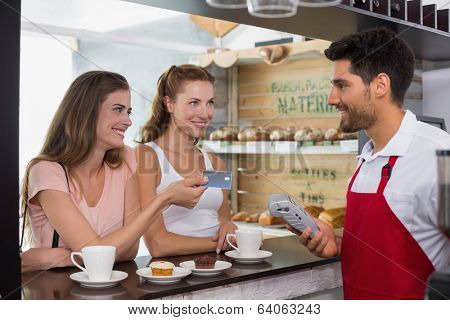 Smiling young friends with woman holding out credit card at the coffee shop