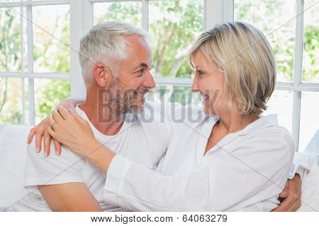 Loving happy mature couple with arm around sitting in bed at home