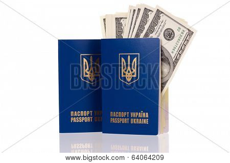 Two international Ukrainian passport with US dollars banknotes isolated on white background