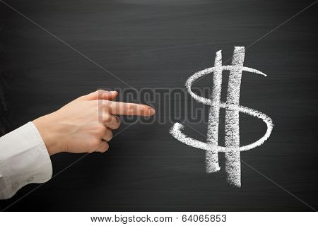 forefinger point at dollar sign on a blackboard