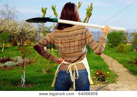 Back view portrait of a woman with shovel in garden