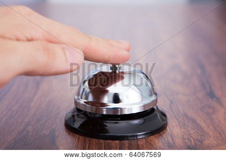 Hand Ringing Service Bell Kept On Wooden Table